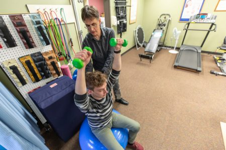 the physical therapy member helps the patient to lift his arms